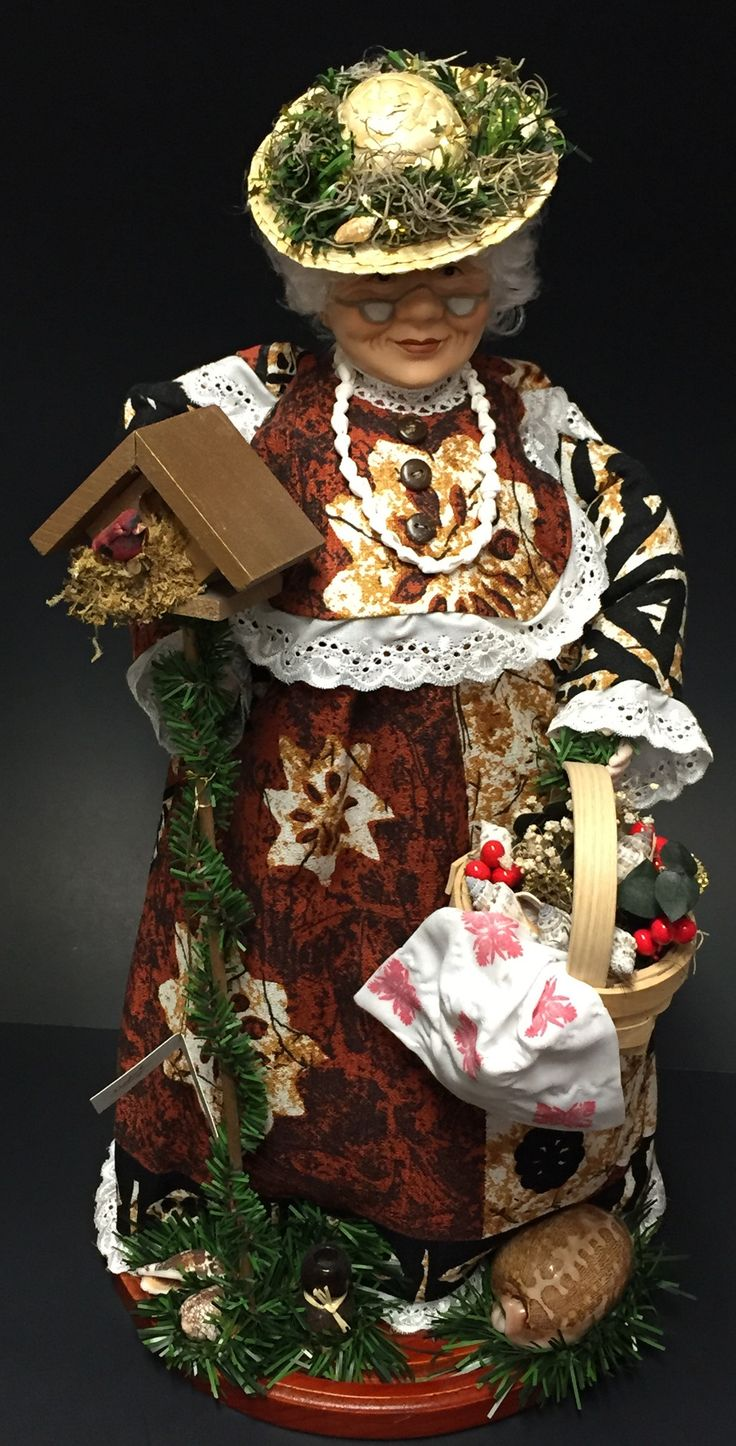 """18-20"""" Tropical Hawaiian Tutu dressed in a """"Tapa"""" patterned muumuu. Holding a bird house, adorned with a shell lei, wearing a straw hat with a green haku on it, carrying a basket full of goodies and s"""
