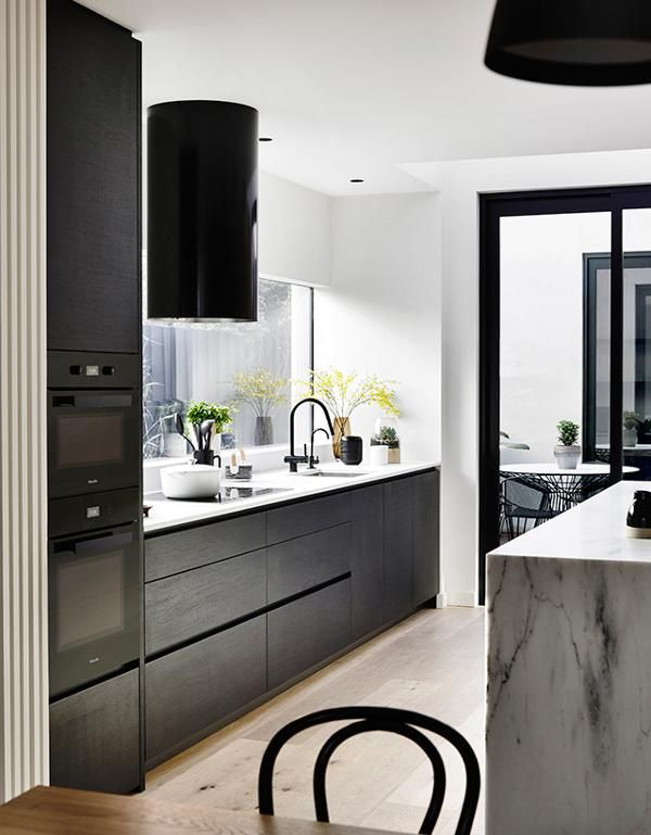 Black kitchen cabinets, white benchtop, black tapware, black appliances, marble island with waterfall edge, thick black window frames, pale timber floorboards, black cylindrical rangehood over window