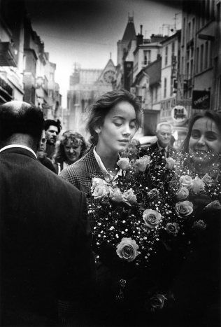 A young woman with a big bunch of roses on the Rue De La Republique in May 1986 in Saint Denis, France. Crédit : Robert DOISNEAU/RAPHO
