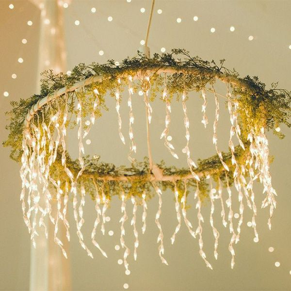Turn a hula hoop into a gorgeous chandelier by wrapping it in twinkling lights and fresh greenery, then suspending it from the ceiling of your venue.