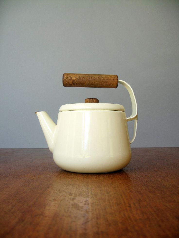 "enamelware teapot, design similar to Dansk Kobenstyle. Creamy white with speckled dark blue interior. Wood handles. Circa 60's or 70's, 6""x6.5""x4.5"""