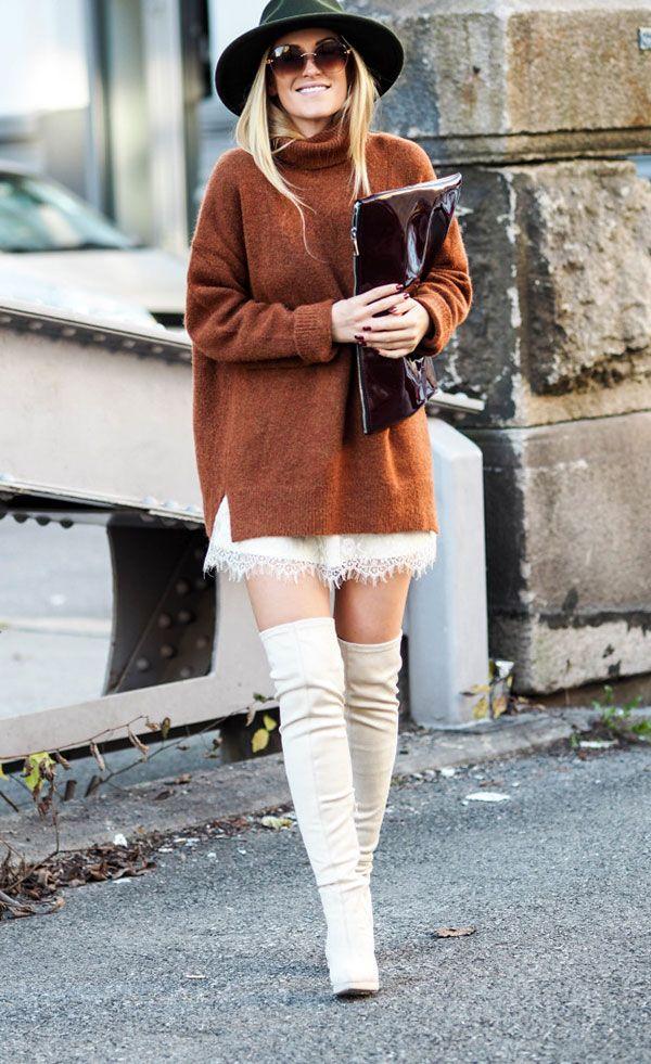 Street style look vestido branco renda com suéter, botas over the knee, chapéu verde e maxi clutch.
