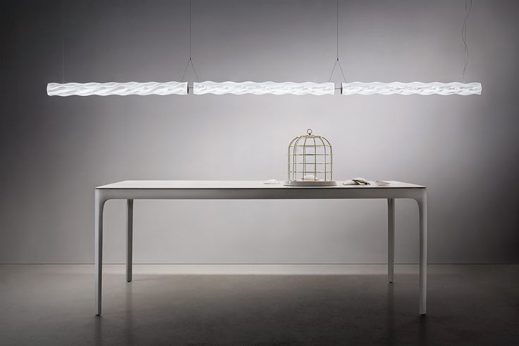 A suspension lamp that flows from one end of a space to another, hung and arranged linearly, slanted, or perpendicular to the ground. Hugo's new, silky white finish is both elegant and versatile, customizing any space with its sinuous design and evenly diffused, soft light, shining through its printed techno-polymer structure. One is free to hang Hugo parallel to the ceiling, or create a series of lamps to fit their desired decorative lighting design. www.slamp.com