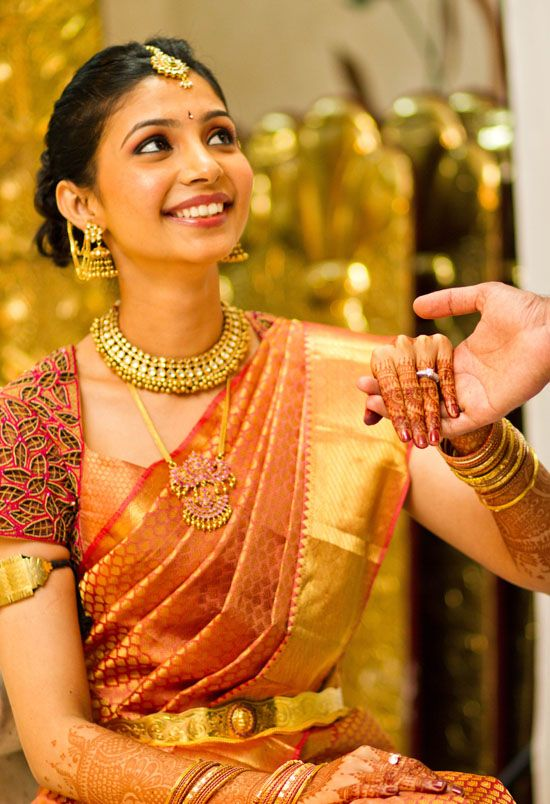Traditional Southern Indian bride wearing bridal saree, jewellery and hairstyle…