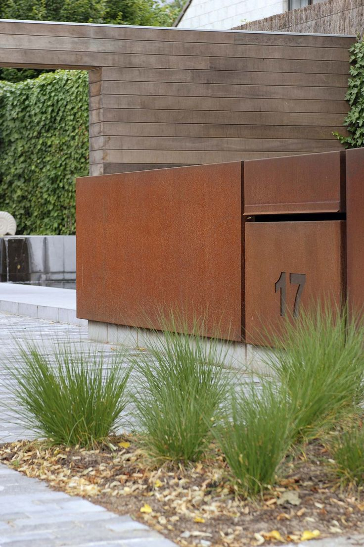 A material mix from CorTen steel and wood creates a contemporary look and feel. Grote strakke tuinen | Filip Van Damme