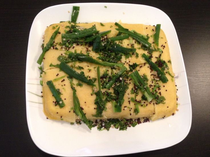 Dhokla - Chick pea flour base cake soaked in sweet and spicy sauce made up of mustard seeds, green chilies, coriander and sugar.