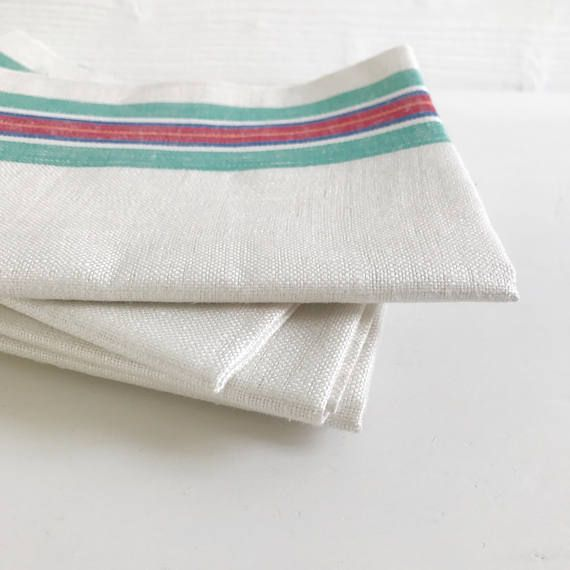 A vintage Irish linen striped teatowel that has never been used or washed. I have a small collection of these teatowels that were presumably to good to use and have been stored in a linen press or over 50 years. There is nothing that puts a shine on your dishes like Irish linen, but these could equally be used as table linens or repurposed in a sewing project. 54cm wide x 76cm long. The green, blue and red stripe measures 5cm wide and runs along both edges. This listing is for one…