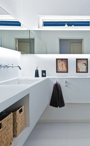 """Solução em branco. O banheiro também recebeubancada e pia de concreto armado coberto de cimento queimado branco, criando uma linguagem comum para as áreas molhadas da casa. Atrás dos espelhos, as lâmpadas fluorescentes de 3 mil k (de tonalidade amarelada ) criam um ambiente agradável e discreto. Nas paredes, tinta epóxi (Suvinil). """"Não deixei nenhum azulejo na casa"""", diz Enrico."""
