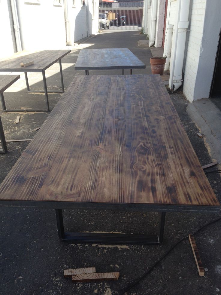 Rustic and charred pine tables in rough steel bases