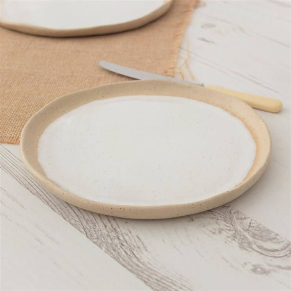 This contemporary side plate has been hand formed and glazed in a simple white glaze. I have left the outer rim and underneath unglazed in order to create a striking contrast between the clean, white glaze and natural, raw clay. It would make a lovely addition to an existing, simple dinner service or alternatively can be used as a small decorative serving plate. These are not perfect factory formed plates- as with any hand built item there will be some variation in size between pieces, which…