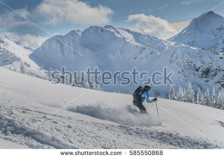 Freeride ski touring skier with airbag skiing deep powder in alpine backcountry heli-skiing cat skiing with views of steep mountains