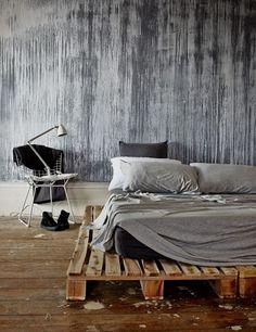 Une chambre avec des coulures de peinture au mur et un lit en palettes de bois