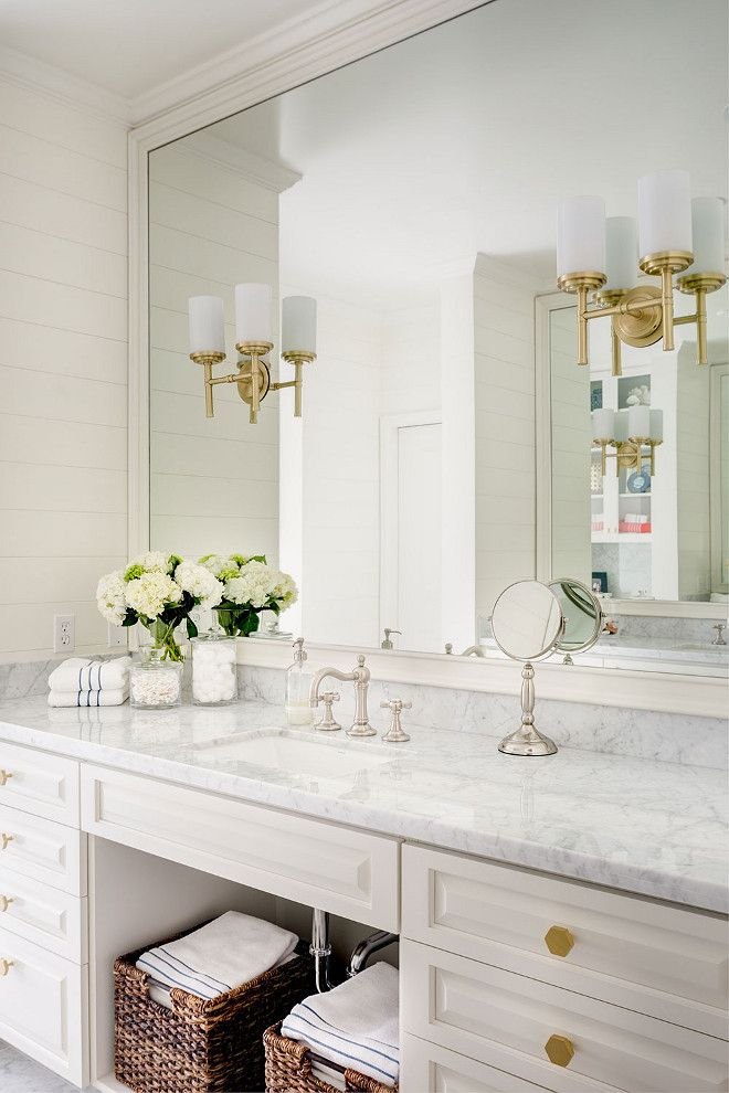 glamorous bathroom showcases a white vanity fitted with goldu2026