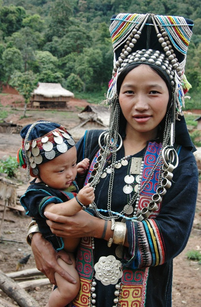 "Laos | ""This Akha Nuqui infant sports a cap colorfully embroidered and adorned with coins and talismans for luck and safekeeping. When she reaches adolescence and weds, she will change roles, adopting the sail-like headdress of her mother."" 