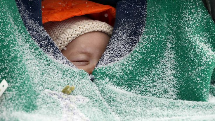 Two-month-old Jack Hsi takes a nap sheltered in his baby carrier while snow falls in Boston, Thursday, Jan. 2, 2014.
