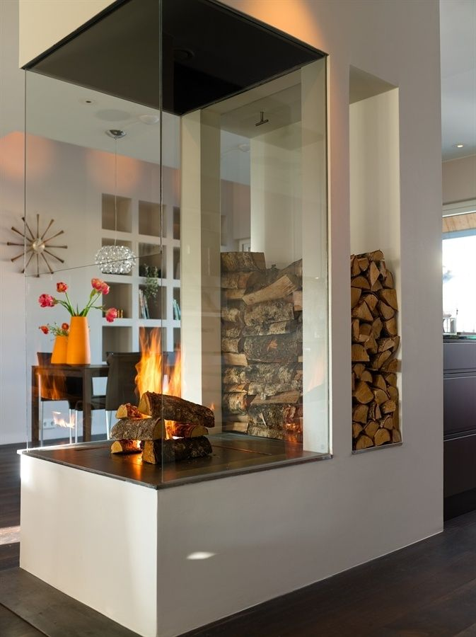 25 Cool Firewood Storage Designs For Modern Homes Highly modern and glamorous, this fireplace is surrounded by glass walls and the pile of wood becomes a design feature in the background.