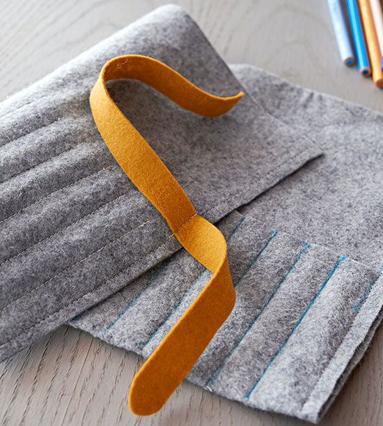Step 3: Sew along each line, backstitching at the beginning and end of each row for added durability. To make a tie, sew a 9×1-1/2 -inch felt strip to one side of the pencil roll short edge.