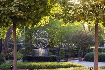 David Harber-stainless steel armillary mounted on stainless steel round plinth, surrounded by boxwood