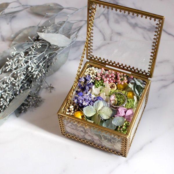 真鍮で縁取られたアンティークな雰囲気でオシャレなデザインの ガラスボックスにドライフラワーやプリザーブドフワラーを アレンジしたオリジナルのリングピローボックス。  重量感のあるデザインのガラスケースは、挙式後もインテリアとして 飾っていただけます。