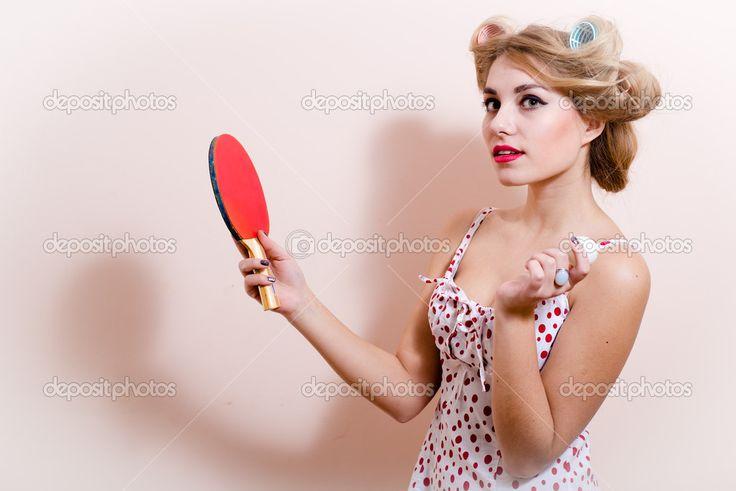 Портрет девушки pinup элегантный привлекательный гламура, изумленно глядя на камеру позирует в красном платье с цветком в волосах & Холдинг битой мяч для настольного тенниса на копии белого или светлого фона пространства крупным планом — стоковое изображение #53104015