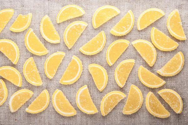 Цукаты из лимонных долек. Лимоны 700гр. Вода 400мл. Сахар 700гр. Сах.пудра Лимоны тщательно моют и на 40-50 минут замачивают в холодной воде. Нарезать кольцами толщиной около 0,5 см Из воды и сахара готовят сироп, в котором лимоны отваривают около получаса. Затем лимонные дольки оставить (примерно 30 минут) настояться в сиропе. Достать, откинуть на дуршлаг и дать стечь оставшемуся сиропу. Выложить на бумагу для выпекания и оставляют подсохнуть, слегка посыпав сахарной пудрой.