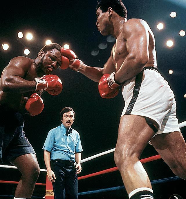 """The Thrilla in Manila""-- Ali/Frazier III. Muhammad Ali defeats Joe Frazier in a brutal bout to retain the heavyweight boxing title."