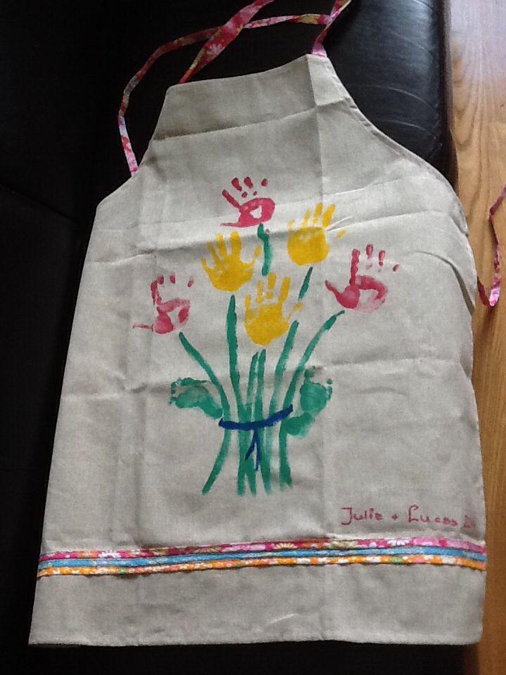Een schort met daarop de handafdruk van kleindochter en voetafdruk van kleinzoon. Een origineel cadeau!