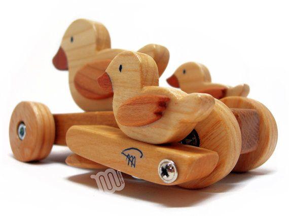 Lindo pato con los patitos, hecho a mano en madera. Regalo perfecto para niños o bebés.  El juguete está provisto de ruedas y tiene un mecanismo elíptico que hace pivotar hacia adelante y hacia atrás los patitos cuando se mueve. La madera es realmente agradable al tacto. En la parte delantera del juguete es un tornillo de ojal por lo que puedes poner una cuerda para arrastrar el juguete; Usted puede simplemente empujarlo demasiado.   Materiales Ceniza, caoba, cerezo madera, cal, acabado a la…