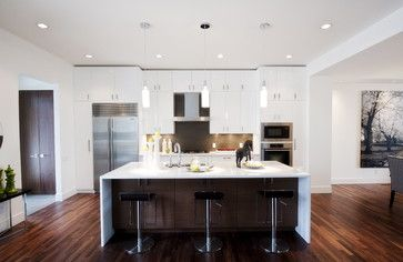 Dark wood outward cabinet facing on the island with white countertops with the waterfall effect.