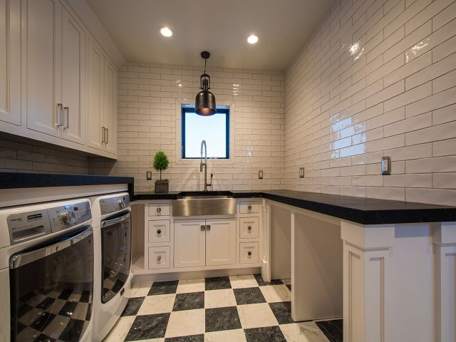 Black and white laundry room features white cabinets suspended over an enclosed washer and dryer facing a folding station topped with black countertops fitted with open storage perfect for doggy beds atop a black and white checkered tiled floor.