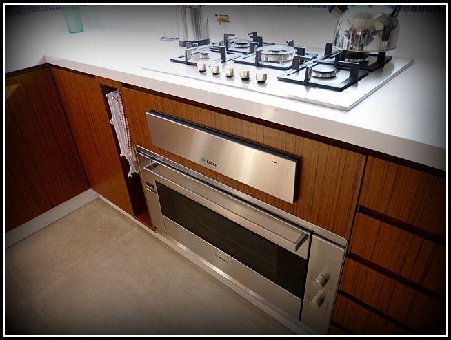 Cocina enchapada. Cubierta Silestone, puertas con tirador oculto o en 45°. Horno y calienta platos.
