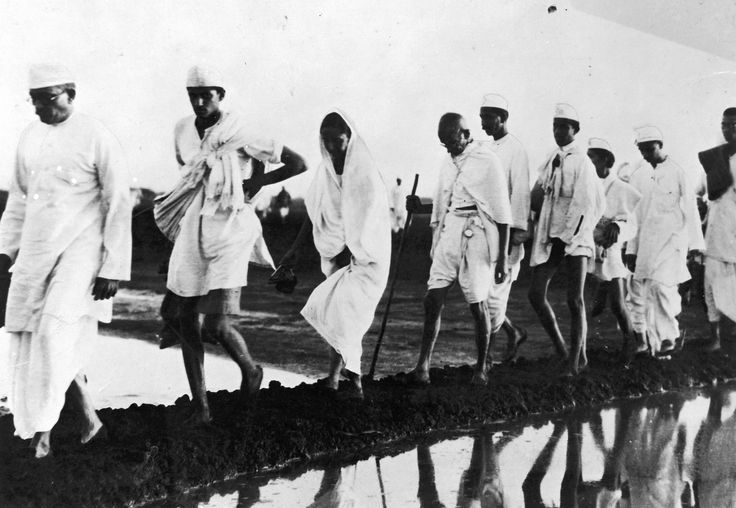 Gandhi walking with followers on the Salt March towards Dandi, with the intention of breaking the English-backed salt laws.