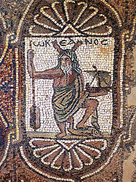 Représentation d'Océan, surmonté de son nom grec ΩΚΕΑΝΟϹ, avec ses attributs habituels : pinces de crustacé sur la tête et rame à la main, auxquelles ont été rajoutés ici un navire et un dauphin. Pétra(Jordanie), église, aile sud, mosaïque, vie siècle