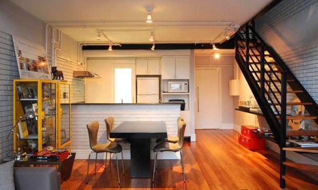 Uma solução para deixar tanto a cozinha quanto a sala mais amplas é integrar os dois ambientes com uma bancada. A mesa encostada no balcão otimiza o espaço.