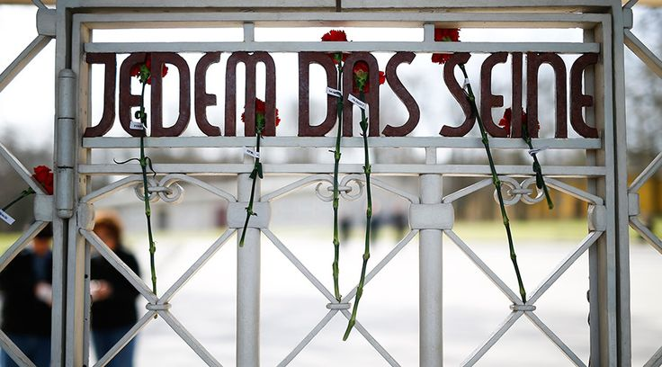 Former Nazi concentration camp Buchenwald becomes home to… refugees? http://sumo.ly/88oI  Red carnations are attached over the slogan 'Jedem das Seine' meaning 'Each to his own' at the internal side of the main gate of former Buchenwald concentration camp near Weimar © Kai Pfaffenbach