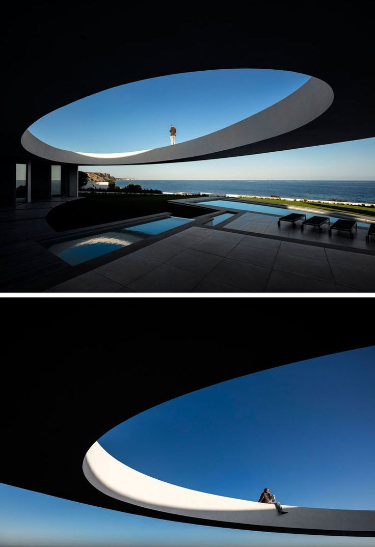 This modern house has a large ellipse cut out of a section of the design to create a sculptural design.