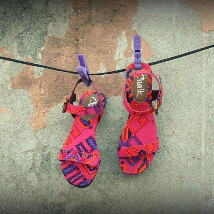 This is a pair of bright fuchsia sandals with colorful pixelated print. The sandals have a single strap with an ankle strap buckle closure.