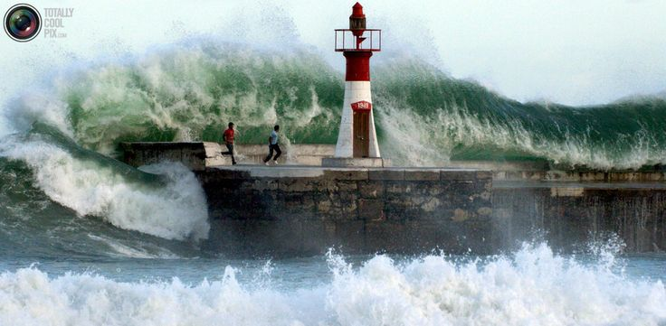Giant waves crash over onlookers washing them off the sea wall of Cape Town's Kalk Bay harbour, August 27, 2005. The two men were later rescued as storms created waves of an estimated nine metres. Picture taken August 27, 2005. REUTERS/Philip Massie