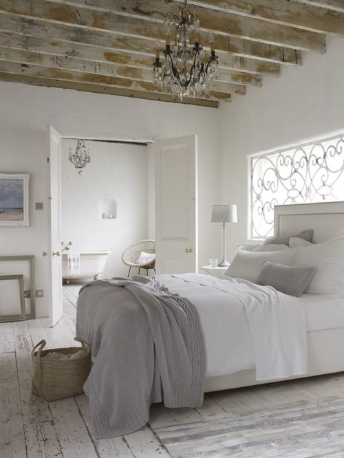 Beautiful rustic flooring provides a nice backdrop for the whites and grays of this little hide a way. The scrollwork on the windows & chandelier hung from the unfinished wood beams add a level of refinement to the space.