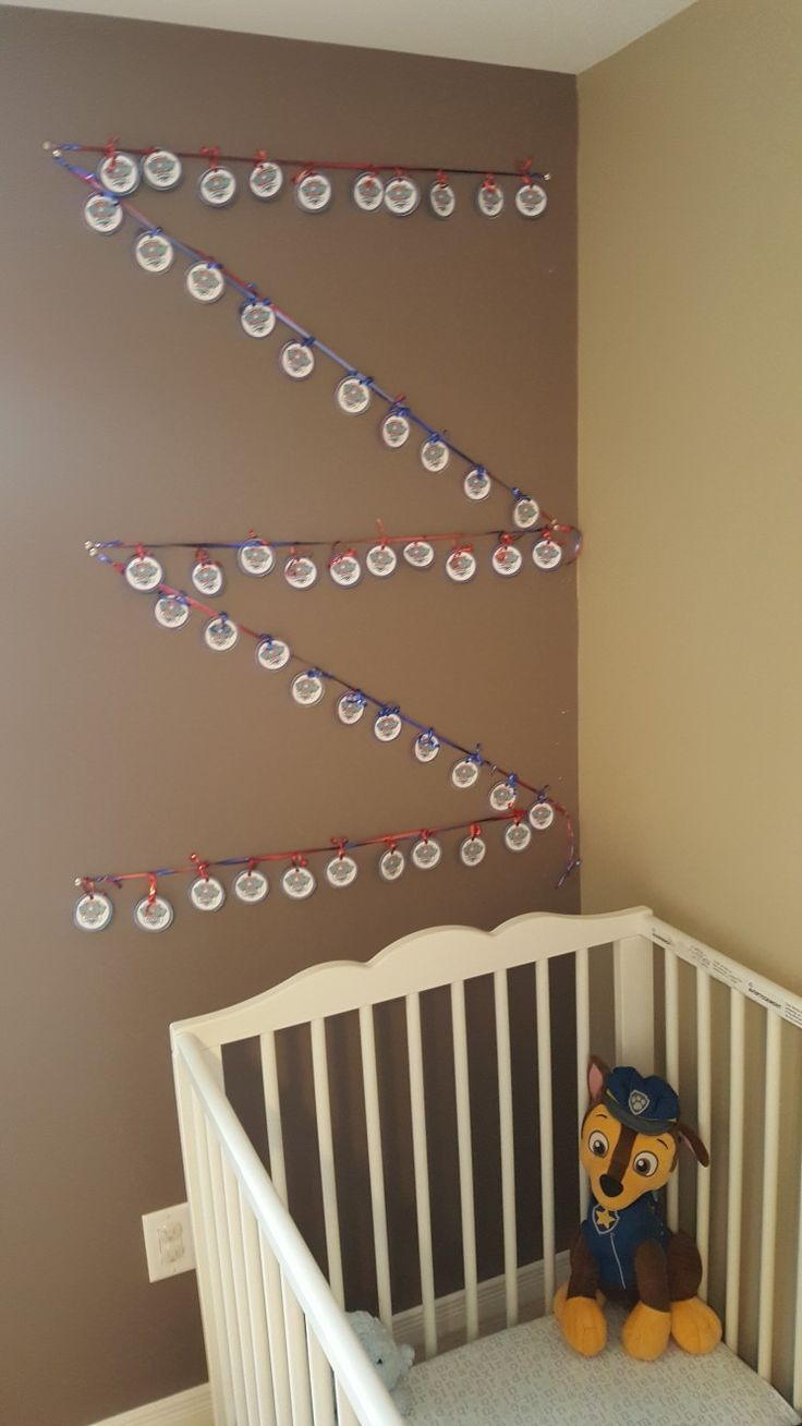 Nursery or baby room decor--DIY print out Paw Patrol tags free printables and put through ribbons red and blue to hang up. Ribbons purchased from Dollarama dollar store. Hang anyway you like.