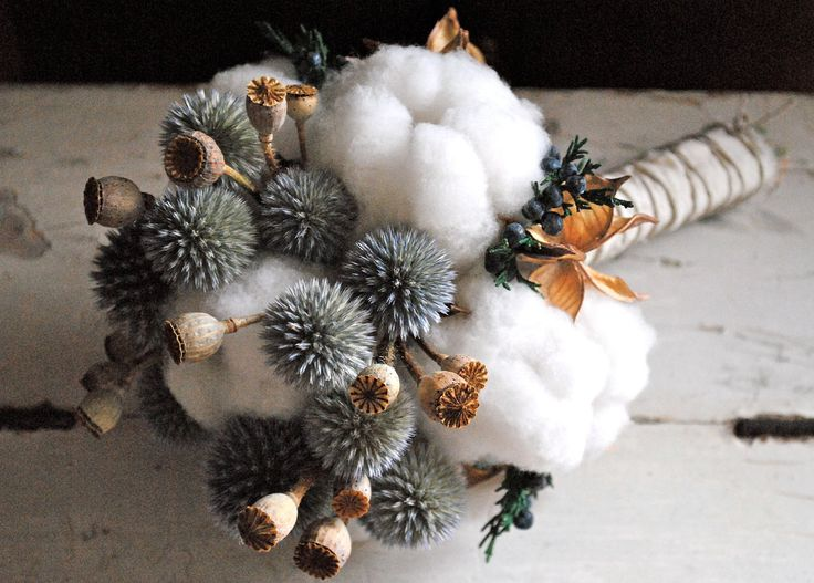 Natural cotton bolls, cotton burs, echinops (globe thistle), mini poppy pods (non opiate variety), and juniper with blue berries.