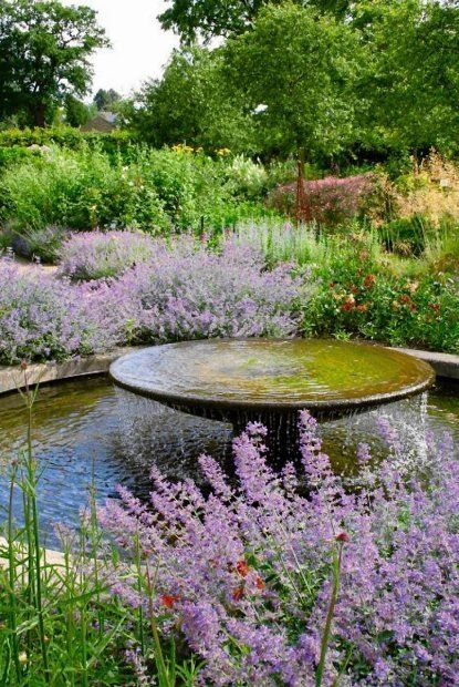 Round disk water feature, overflowing into pool.