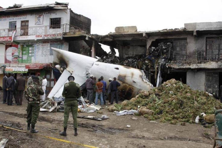 Soldiers and airport staff members look at the wreckage of the Fokker 50 cargo plane after it crashed shortly after takeoff at Kenyatta International Airport