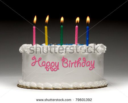 "White birthday cake profile on gradient background with five colorful lit candles and ""Happy Birthday"" written on the side with frosting - stock photo"