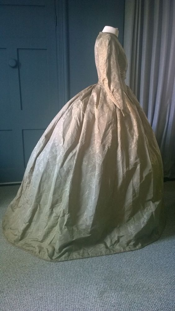 From the merchant's listing:   A statuesque crinoline day dress, dating to the 1860s. I say statuesque as the dress is quite tall compar...