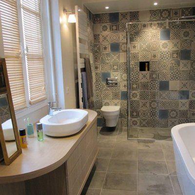 La salle de bains de la chambre principale est personnalisée par un patchwork de carreaux ciment, ponctué par des carreaux unis bleus. Au sol, des carreaux en pierre de Tunisie. Les  courbes du meuble, réalisé sur mesure, s'accordent avec celles de la baignoire en îlot (création Philippe Starck, Duravit) et de la vasque intégrée.