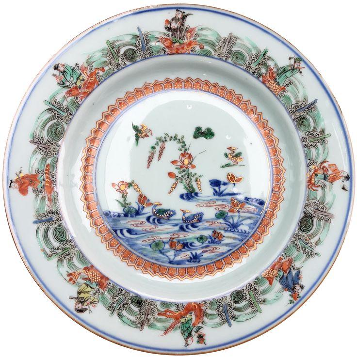 Plat à décor doucai de canards mandarins et des huit immortels taoïstes en porcelaine de Chine de la Compagnie des Indes d'époque Kangxi. Peinte dans les émaux de la famille verte, à décor d'un médaillon central représentant des canards mandarins nageant parmi des lotus. Sur l'aile, les huit immortels taoïstes chevauchant leurs montures fantastiques.