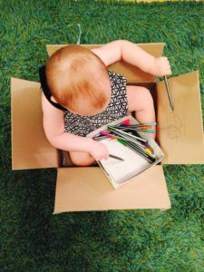 Sitting inside a box and drawing, activities for one year old, development promoting activities for toddlers, toddler games, activities for 12 month old, activities for 13 month old, activities for 14 month old, activities for 15 month old, activities for 16 month old, activities for 17 month old, activities for 18 month old, games for toddler