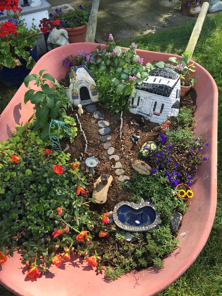 Fairy garden!! Miniatures, painted rocks and succulents make a decorative display in a wheelbarrow by Joanne Sobeck