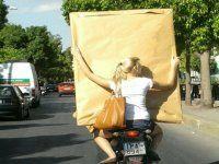 """Ασκήσεις ισορροπίας πάνω στη μοτοσυκλέτα κάνει η κοπέλα, η οποία κρατά στα χέρια της ένα τεράστιο κάδρο.  Ανεβάστε τα """"στραβά και παράδοξα"""" που εσείς συναντάτε στο: http://www.autoreport.gr/blog/post_add"""